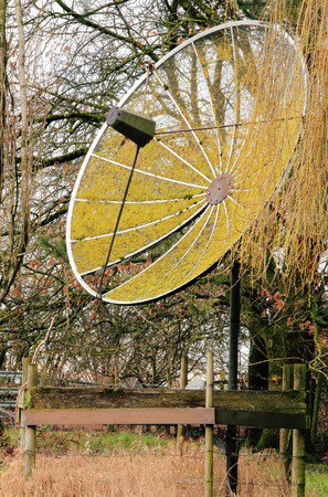 neglected: An old satellite dish, once used for receiving broadcast signals, sits moldy and neglected in a backyard. Stock Photo