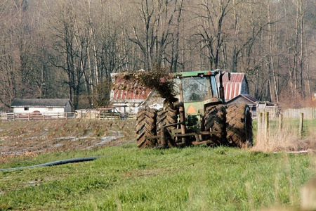 outside machines: Liquid manure is spread on a field to fertilize it using a tractor and hose.