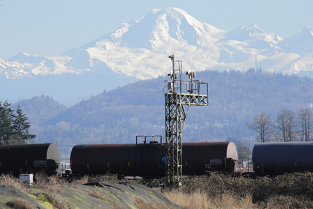 snow capped mountain: Petroleum oil tankers are transported past a snow capped mountain Stock Photo