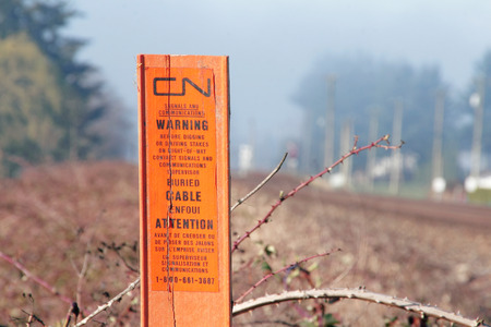 warns: A post erected by Canadian National Railway warns that cables are buried near the tracks. Editorial