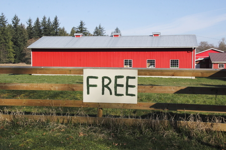 posted: A sign in bold, black lettering is posted on a gate in front of a farm.