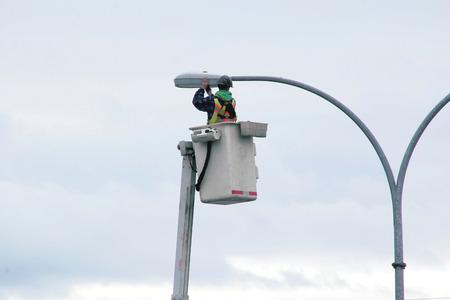 hoist: A technician uses a hoist to change city street lights.