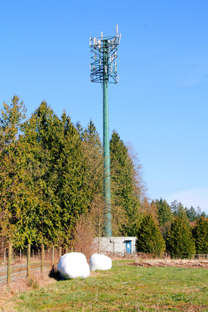 tec: A multi-receiver and sending transmission tower in a rural setting.