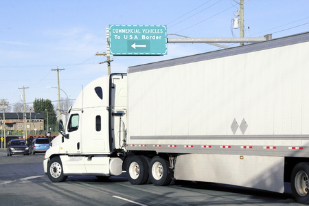 Large trucks use a commercial vehicle lane to import goods into the United States. Stock Photo