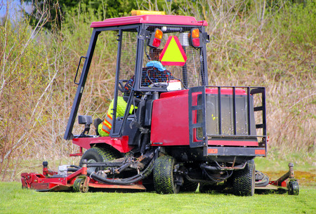 City crew use an industrial lawn or grass cutter to maintain civic property.