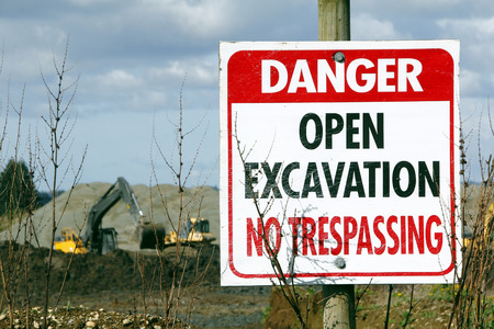 not open: A sign warns that a gravel pit is an open excavation and that trespassing is not allowed.