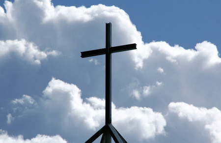 larger than life: Close on a Christian cross with billowing cumulus clouds as a backdrop.