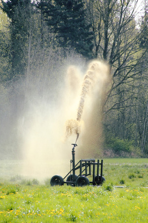 Liquid manure is used to fertilize a field of grass in Washington State. Stock Photo