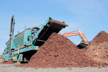 machines: A machine is used to break down wood into small chips for agricultural purposes.
