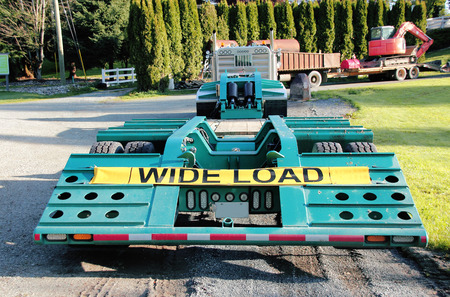semi trailer: A flatbed semi trailer with a sign the reads wide load.
