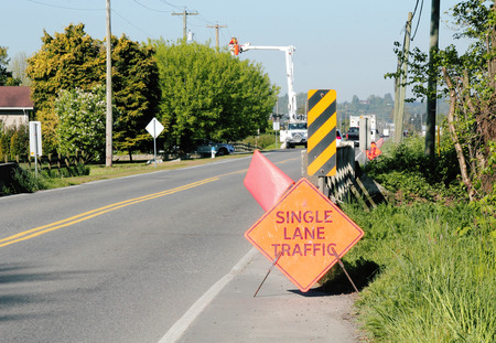 single lane road: A hydro crew works on a public road with signs and flags used to promote safety in the area. Stock Photo