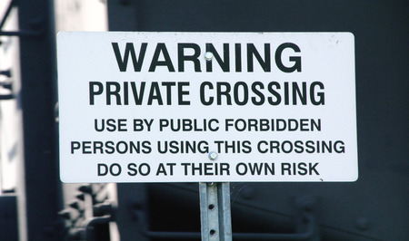 warns: A sign warns that the crossing is private as a train passes in the background.