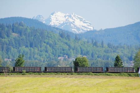 materia prima: Un treno trasporta materie prime attraverso una regione montuosa. Archivio Fotografico