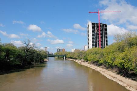 riverfront: Construction crane and development along a riverfront.
