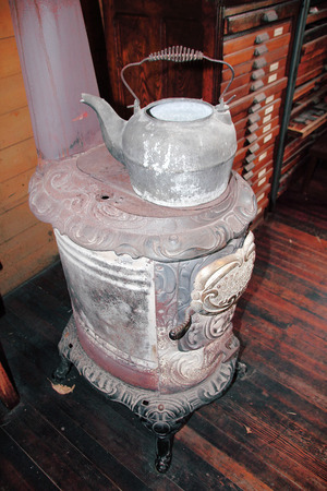 pot belly: An old fashioned kettle sits on top of a pot belly stove. Stock Photo