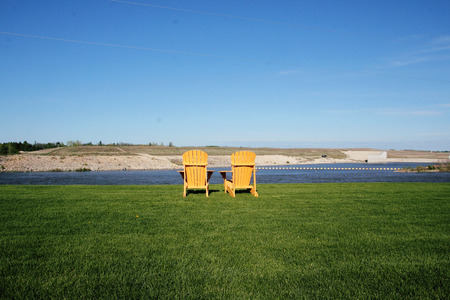 lakefront: Two simple comfortable outdoor chairs on a lakefront setting. Stock Photo
