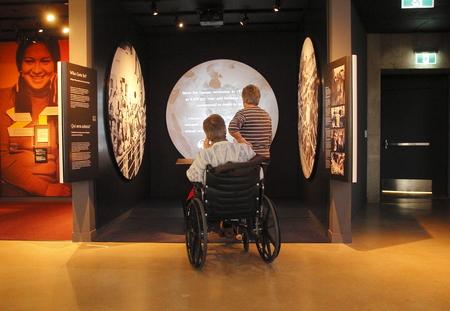 휠체어를 타고있는 한 남자가 위니펙의 인권 박물관에서 인권에 대해 읽고 알아 봅니다.