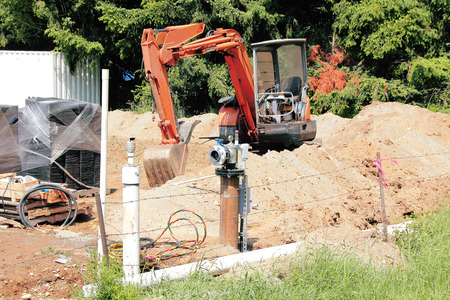 dig: Equipment is used to dig a channel for a small residential pipeline that feeds Natural Gas.