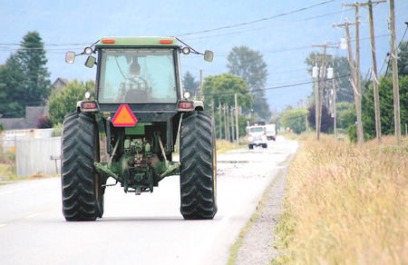 A large tractor is equipped with a safety deflector to help maintain visibility and caution. Stock Photo