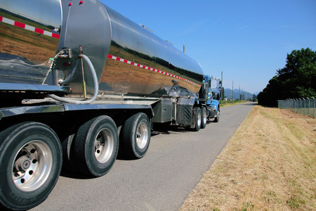 A specialized vehicle hauls stainless steal tankers to pick up milk from rural farms.
