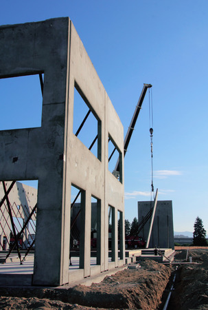 An industrial hoist or crane is used to position a precast concrete wall into place.