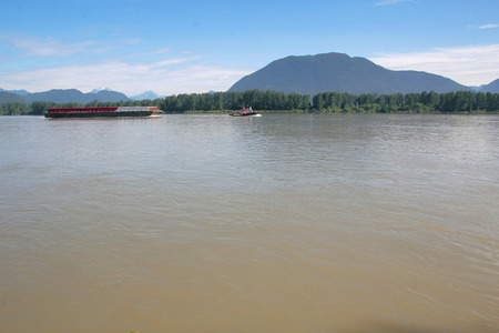 fraser river: A tug pulls a barge on the Fraser River in British Columbia Canada.