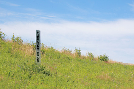 unobtrusive: A simple unobtrusive sign indicates where an oil pipeline is buried.