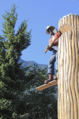 tree cutting: Statue of a traditional lumberjack cutting down a tree