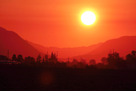 extreme heat: An intense sun rises above the valley. Stock Photo