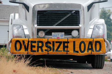 front bumper: A sign mounted on the front bumper of a rig states that its hauling an oversized item.