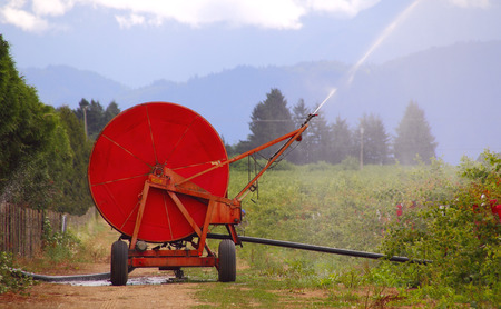 irrigate: A large spindle or reel is used to transport hoses that will irrigate farm crops Stock Photo