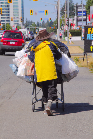 homeless person: A homeless person pushes a shopping cart down a busy street in Abbotsford, BC, Canada on July 28, 2015. Editorial