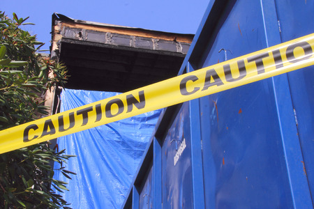 surrounds: Caution tape surrounds an apartment destroyed by fire. Stock Photo