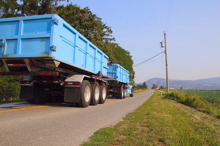 dispose: A large industrial truck is used to transport and dispose of waste material.