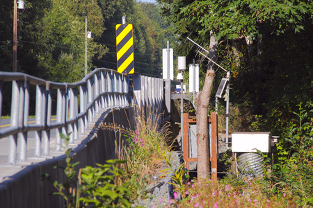 Instrumentation: Instrumentation, used to gauge water quality and flow, is mounted on the side of a bridge crossing the salmon stream.