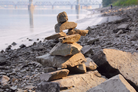 inukshuk: Medium shot of a traditional Canadian Inuit Inukshuk on a river shoreline. Stock Photo