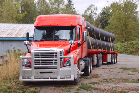strapped: A long and large semi trailer truck hauling conduit on two flatbeds. Stock Photo