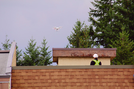 A technician flies a drone to inspect an apartment roof in need of repair. Stock Photo