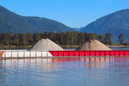 産業川のはしけは、建設に使用される材料の山を運ぶ。
