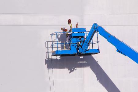 높은 고도에 도달하는 리프트 또는 크레인을 사용하는 화가의 중간 샷.