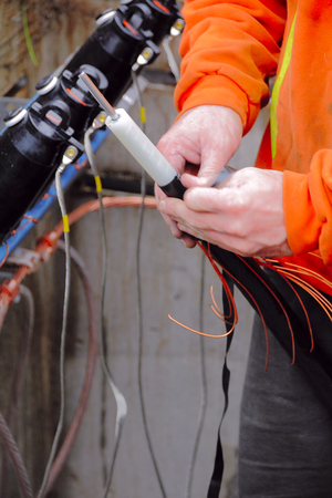 taping: Close on electricians hands taping cables used for a new underground electrical distribution facility.