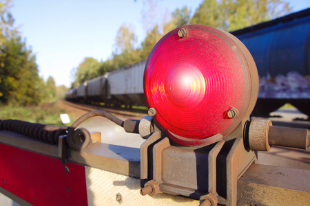 proceed: Warning light attached to a railway crossing gate.