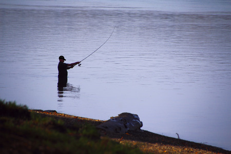 recreational: Silhouette of recreational fisherman standing in a lake casting his line.