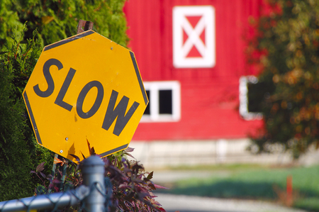 proceed: A black and yellow sign asks motorists to slow down when entering the driveway. Stock Photo