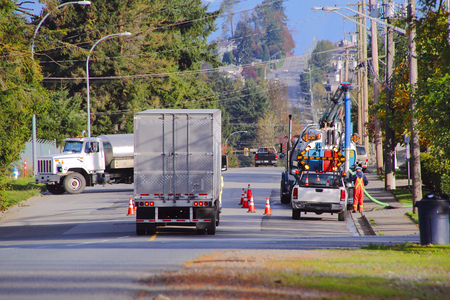 Cones divert trucks as city workers clean the sewers