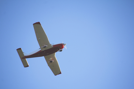 underbelly: Underbelly of a flying single engine plane against a blue background.