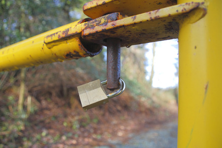 ensures: A padlock ensures a gate leading to property cant be opened. Stock Photo