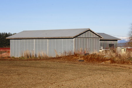 dormant: An old metal farm building, still in use, stands beside a dormant field. Stock Photo