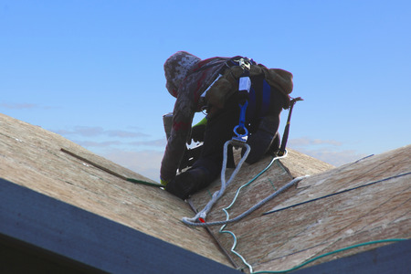 roofer: A roofer wears a safety belt and rope to prevent serious injuries.