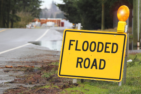 A bright yellow sign warns motorists that the road is flooded.
